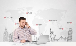 20687182 - handsome young businessman with world map and major landmarks of the world